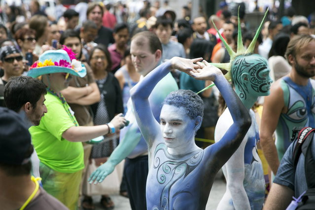 Crist Crow stretches after being painted at Columbus Circle as body-painting artists gathered to decorate nude models as part of an event featuring artist Andy Golub, Saturday, July 26, 2014, in New York. Golub's event Saturday included a post-painting march down Broadway and a return to Times Square for a photo shoot. (Photo by John Minchillo/AP Photo)