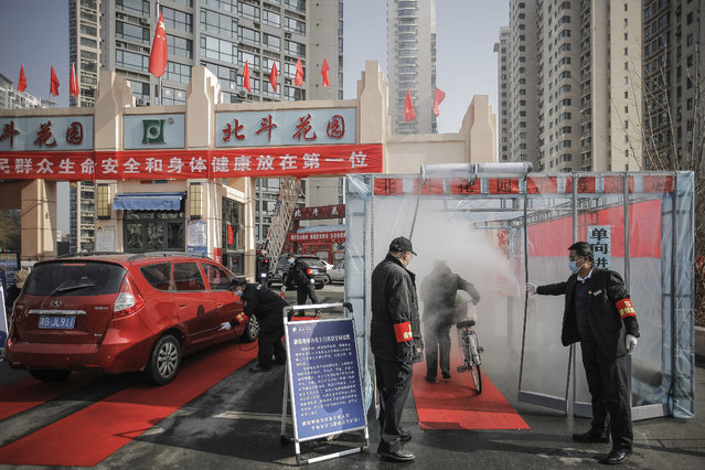 Security guards hold the curtain for a cyclist to past through a disinfectant spray in order to return home at a residential complex in northern China's Tianjin Municipality Tuesday, February 11, 2020. China's daily death toll from a new virus topped 100 for the first time and pushed the total past 1,000 dead, authorities said Tuesday after leader Xi Jinping visited a health center to rally public morale amid little sign the contagion is abating. (Photo by Chinatopix via AP Photo)