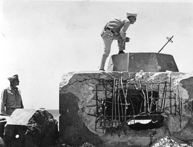 Commander Harrison looks in Jap pillbox, while Captain Zacharias watches