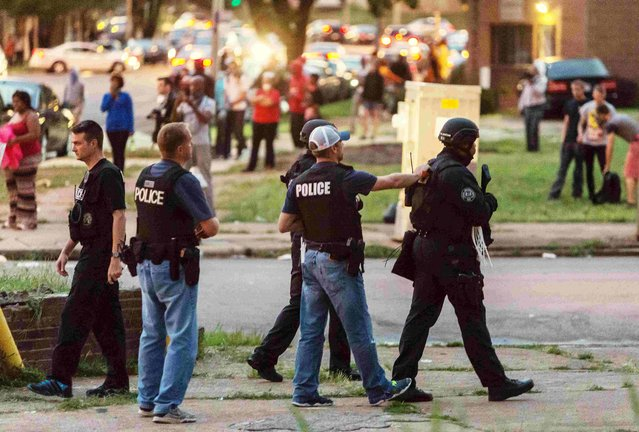 Police monitor the crowd as protesters gathered after a shooting incident in St. Louis, Missouri August 19, 2015. (Photo by Kenny Bahr/Reuters)