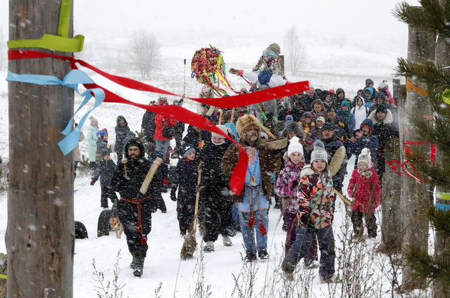 People carry a figure representing the Lady Maslenitsa during the Maslenitsa (Shrovetide) festival at the Suoranda hills outside St. Petersburg, Russia, 01 March 2020. (Photo by Anatoly Maltsev/EPA/EFE)