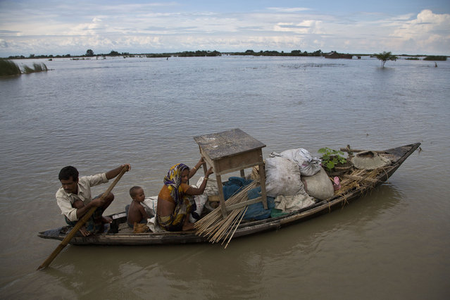 An Indian family sail through a flood-affected area in Xandohkhaitee village, about 80 kilometers (50 miles) east of Gauhati, India , Saturday, August 22, 2015. (Photo by Anupam Nath/AP Photo)