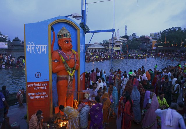 Devotees pray in front of an idol of the Hindu monkey god Hanuman, on the banks of Godavari river during Kumbh Mela or the Pitcher Festival in Nashik, India, August 26, 2015. (Photo by Danish Siddiqui/Reuters)