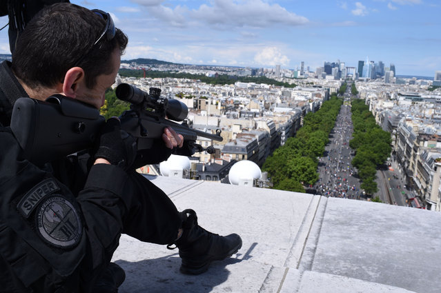 A sniper of the French 'Brigade d'Intervention' takes up his position at the top of the Arc de Triomphe during the annual Bastille Day military parade on the Champs-Elysees avenue in Paris on July 14, 2016. France holds annual Bastille Day military parade with troops from Australia and New Zealand as special guests among the 3,000 soldiers who will march up the Champs Elysees avenue. They will be accompanied by 200 vehicles with 85 aircraft flying overhead. (Photo by Stephane De Sakutin/AFP Photo)