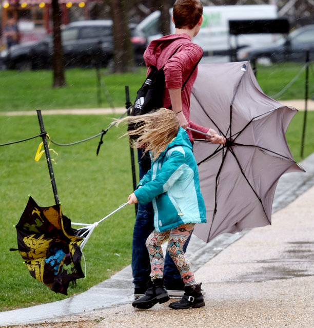 Pedestrians respond to a micro-burst of wind in Washington, DC on April 6, 2017. The wind caused some damage throughout the city. (Photo by Bonnie Jo Mount/The Washington Post)