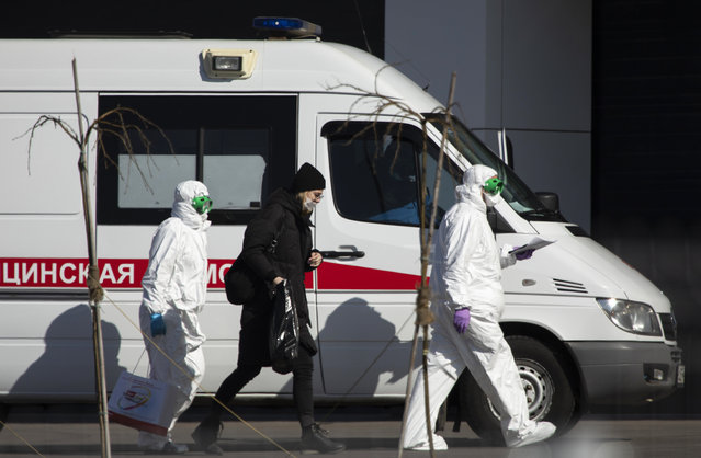 Medical workers escort a woman, suspected of having the coronavirus infection, to get out from an ambulance to the hospital for coronavirus patients in Kommunarka, outside Moscow, Russia, Tuesday, March 24, 2020, with Russia only reporting a few hundred virus cases. The highly contagious COVID-19 coronavirus can cause mild symptoms, but for some it can cause severe illness including pneumonia. (Photo by Pavel Golovkin/AP Photo)