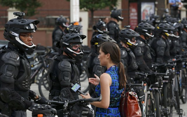 "A reporter talks to police dressed in tactical gear as they block a downtown street during a march by various groups, including ""Black Lives Matter"" and ""Shut Down Trump and the RNC"" ahead of the Republican National Convention in Cleveland, Ohio, U.S. July 17, 2016. (Photo by Lucas Jackson/Reuters)"