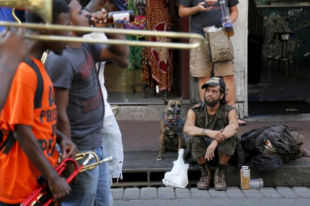 A man and his dog watch a brass band perform on Bourbon Street one day before the ten year anniversary of Hurricane Katrina in New Orleans, Louisiana, August 28, 2015. (Photo by Jonathan Bachman/Reuters)