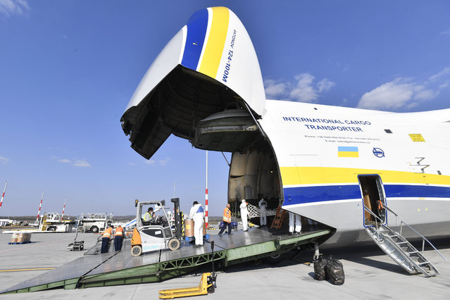 Medical equipment are unloaded from a cargo plane, the world's largest in regular service, from China at Budapest Liszt Ferenc International Airport in Budapest, Hungary, Saturday, April 4, 2020. The delivery is part of a larger shipment of supplies from China aimed at the protection of the people and health workers against the pandemic of coronavirus.(Photo by Zoltan Mathe/MTI via AP Photo)