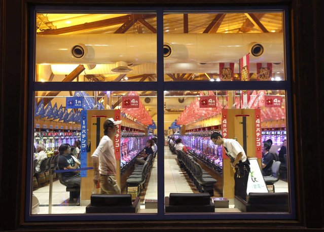 People are seen through windows at a Dynam pachinko parlour in Honjo, north of Tokyo August 4, 2014. (Photo by Issei Kato/Reuters)
