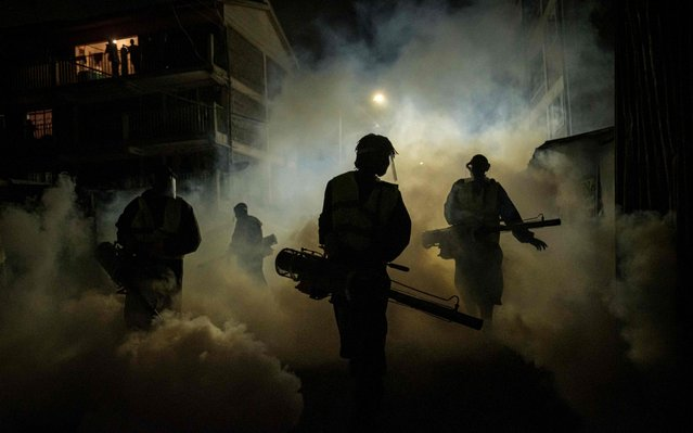 """Volunteers from Sonko Rescue Team, an NGO privately funded by Nairobi Governor Mike Sonko, fumigate a street to curb the spread of COVID-19 during a joint operation with Nairobi county during a 7pm-5am curfew at a residential area in Nairobi, Kenya, on April 6, 2020. Kenyan President Uhuru Kenyatta on April 6 imposed a three-week ban on movement in and out of four main coronavirus """"infected areas"""", including the capital Nairobi, ahead of the usually busy Easter weekend. Kenya currently counts 158 cases and six deaths from the virus, most of them in the capital, with a few cases also along the coast. (Photo by Yasuyoshi Chiba/AFP Photo)"""
