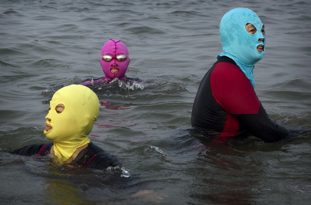 Chinese women wear face-kinis as they swim on August 22, 2014 on the Yellow Sea in Qingdao, China. The locally designed mask is worn by many local women to protect them from jellyfish stings, algae and the sun's ultraviolet rays. (Photo by Kevin Frayer/Getty Images)