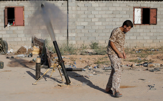 A fighter of Libyan forces allied with the U.N.-backed government fires a 81 mm mortar round in Sirte, Libya, July 26, 2016. (Photo by Goran Tomasevic/Reuters)