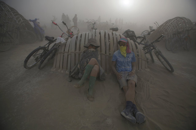 "KK Franks and her husband Jordy Franks rest during a dust storm at the Burning Man 2015 ""Carnival of Mirrors"" arts and music festival in the Black Rock Desert of Nevada, September 2, 2015. (Photo by Jim Urquhart/Reuters)"