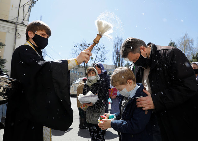 A clergyman wearing a protective face mask sprinkles holy water on believers during a ceremony to bless Easter cakes and eggs on the eve of the Orthodox Easter, amid the coronavirus disease (COVID-19) outbreak in Stavropol, Russia on April 18, 2020. (Photo by Eduard Korniyenko/Reuters)