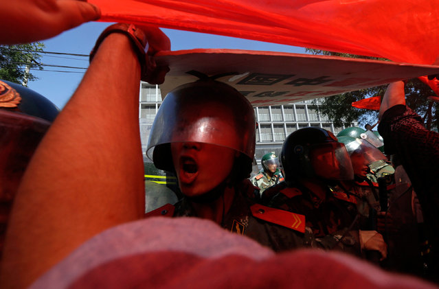 A Chinese paramilitary policeman reacts as a giant Chinese national flag is pulled by protesters towards the Japanese embassy in Beijing, China, on September 15, 2012. (Photo by Ng Han Guan/AP Photo)