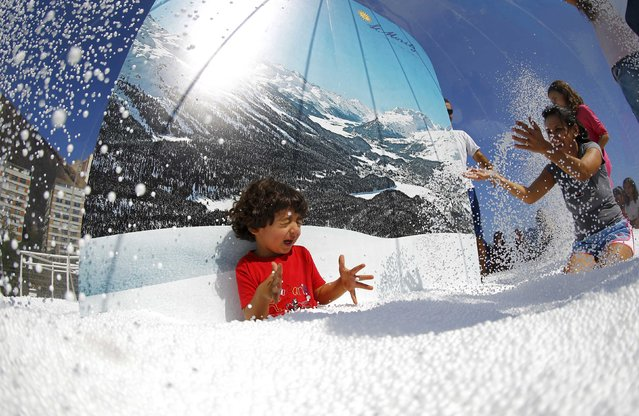 A boy plays in a display at the Switzerland house in Lagoa, Rio de Janeiro, Brazil on August 1, 2016. (Photo by Ivan Alvarado/Reuters)