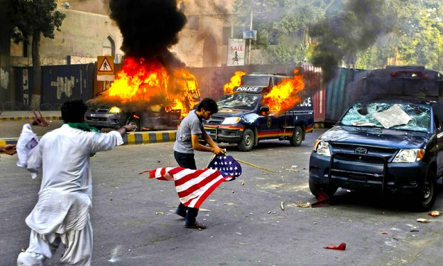 """A protester carries a flag as police vehicles burn in Karachi, Pakistan, on September 21, 2012. Tens of thousands protested against the film around the country after the government encouraged peaceful protests and declared a national holiday """"Love for the Prophet Day"""". Demonstrations turned violent and scores of people were killed died after police opened fire on rioters torching a cinema in the northwest city of Peshawar. (Photo by Fareed Khan/Associated Press)"""
