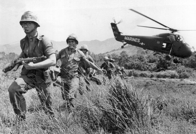 In this April 28, 1965 file photo, U.S. Marine infantry stream into a suspected Viet Cong village near Da Nang in Vietnam during the Vietnamese war. Filmmaker Ken Burns said he hopes his 10-part documentary about the War, which begins September 17, 2017 on PBS, could serve as sort of a vaccine against some problems that took root during the conflict, such as a lack of civil discourse in America. (Photo by Eddie Adams/AP Photo)