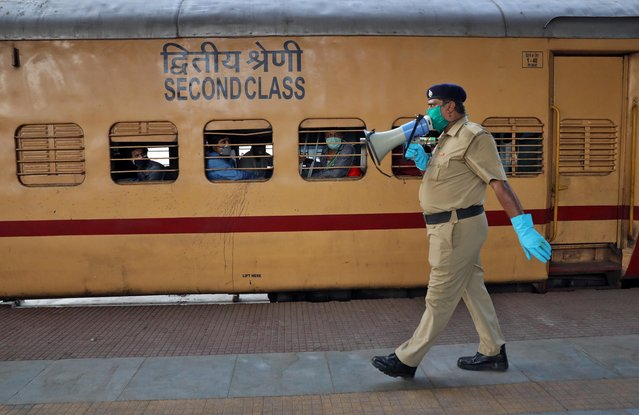 A police officer uses a megaphone to urge people to maintain safe distance upon disembarking from the train that arrived from the southern state of Tamil Nadu after a limited reopening of India's giant rail network following a nearly seven-week lockdown to slow the spreading of the coronavirus disease (COVID-19), at the Howrah Junction railway station on the outskirts of Kolkata, India, May 12, 2020. (Photo by Rupak De Chowdhuri/Reuters)