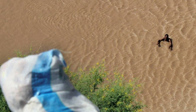 A Pakistani looks at a sack of relief goods dropped from a helicopter in the flooded village of Multan district, Pakistan on Sunday, September 14, 2014. Civil and military officials have been using helicopters and boats to evacuate marooned people since Sept. 3, when floods triggered by monsoon rains hit Pakistan and Kashmir, which is divided between Pakistan and neighboring India. Hundreds of people have died in the flooding. (Photo by Mansoor Abbas/AP Photo)