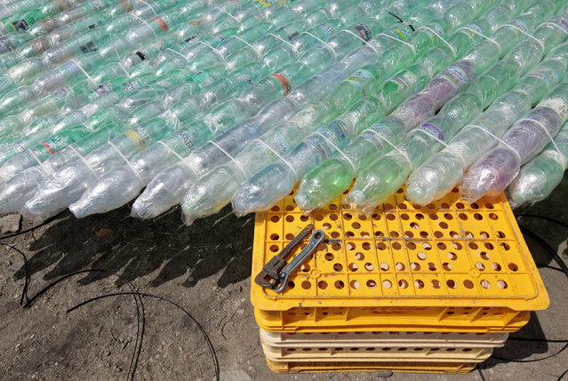 A wrench and strapped plastic bottles are seen in a yard in Nymburk July 1, 2014. (Photo by David W. Cerny/Reuters)