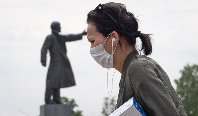 A woman wearing a face mask during a protect against coronavirus infection as she walks past a statue of Soviet Union founder Vladimir Lenin, in Kirovsk, about 30 kilometres (19 miles) east of St.Petersburg, Russia, Monday, June 8, 2020. (Photo by Dmitri Lovetsky/AP Photo)