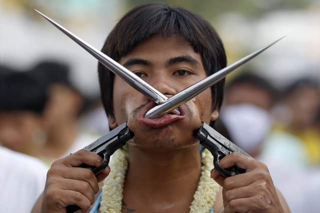 A devotee of the Chinese Bang Neow Shrine with spikes attached to plastic pistols pierced through his cheeks takes part in a procession celebrating the annual vegetarian festival in Phuket September 29, 2014. (Photo by Damir Sagolj/Reuters)