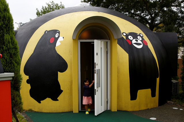 """A girl from Singapore comes out of a quake-resistant dome house decorated with Japan's popular """"Kumamon"""" bear character at the Aso Farm Land resort in Aso, Japan on November 6, 2017. (Photo by Kim Kyung-Hoon/Reuters)"""