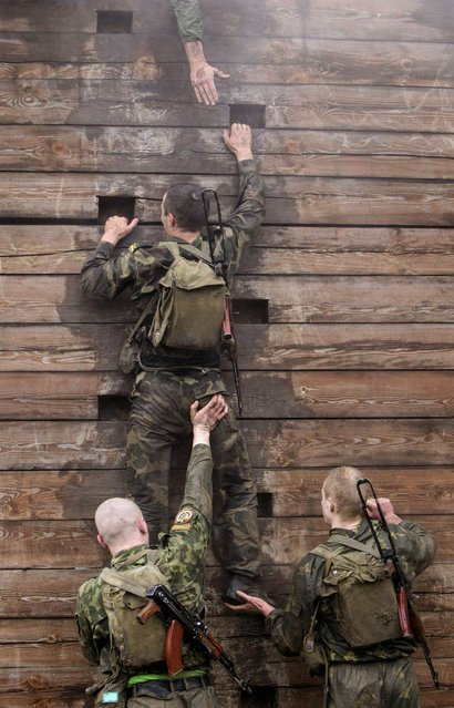 """Servicemen from the Interior Ministry special unit climb a wall as they take part in a test near the village of Gorany, some 32 km (20 miles) west of Minsk, October 23, 2012. Servicemen have to pass several tough tests before being awarded entry to the ministry's elite """"Red Beret"""" unit, according to the ministry. (Photo by Vasily Fedosenko/Reuters)"""