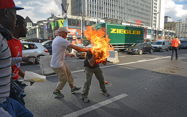 A man sets himself alight during a demonstration of refugees in Brussels, on October 3, 2014. (Photo by Thibault Kruyts/AFP Photo)