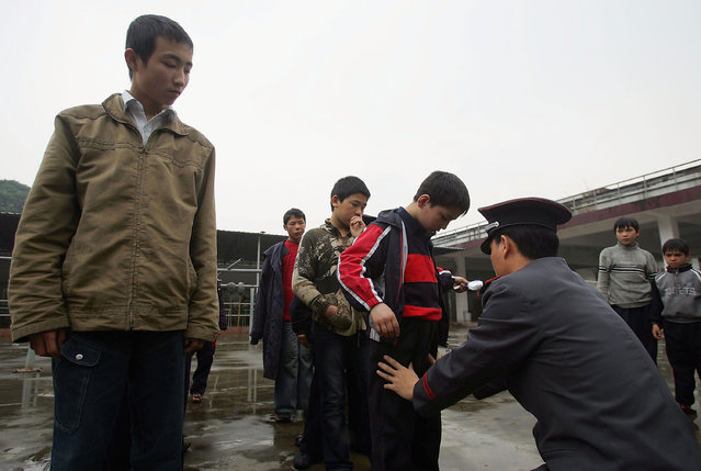 A security guard frisks boys after one kid's money was stolen at an assistance center February 24, 2005 in Shenzhen, Guangdong Province, China. (Photo by Cancan Chu/Getty Images)