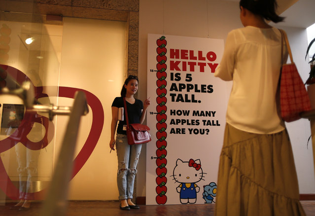 """A woman poses for a photo at the """"Hello! Exploring the Supercute World of Hello Kitty"""" museum exhibit in honor of Hello Kitty's 40th anniversary, at the Japanese American National Museum in Los Angeles, California October 10, 2014. (Photo by Lucy Nicholson/Reuters)"""