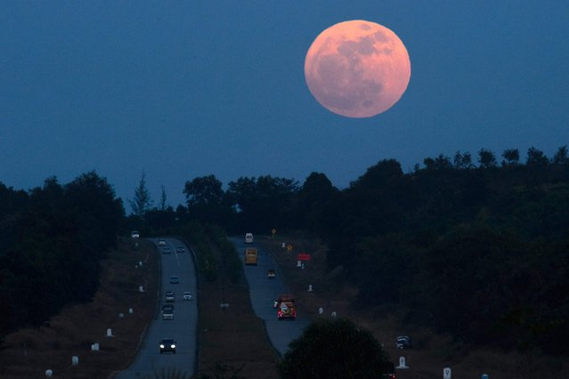 The supermoon rises over a highway near Yangon, Myanmar on December 3, 2017. The lunar phenomenon occurs when a full moon is at its closest point to earth. (Photo by Ye Aung/AFP Photo)