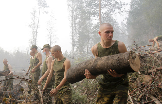 Russian servicemen remove felled trees, which were cut down to prevent new fire outbursts, outside the town of Lukhovitsy, some 110 km (68 miles) southeast of the capital Moscow, August 6, 2010. (Photo by Denis Sinyakov/Reuters)