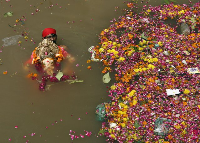 A man holds an idol of the Hindu god Ganesh, the deity of prosperity, in a temporary pond after its immersion during the ten-day-long Ganesh Chaturthi festival in Ahmedabad, India, September 22, 2015. (Photo by Amit Dave/Reuters)