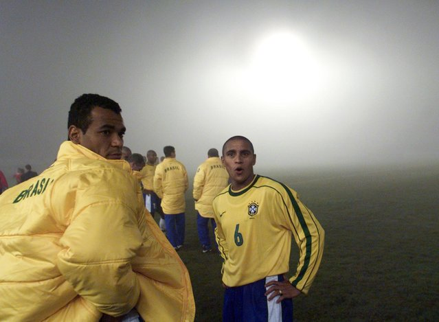 Brazil's Cafu (L) and Roberto Carlos stand together in the fog-covered field after their Copa America game against Chile was suspended by the referee with five minutes left of the second half in Ciudad del Este, Paraguay, July 6, 1999. Brazil were eventually awarded the victory after leading the match 1-0. (Photo by Andrew Winning/Reuters)