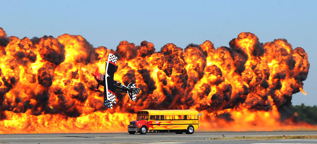 During an act called The Immortals, Skip Stewart flies his aircraft, Prometheus, a variant of a Pitts S-2S adapted for him in knife edge flight with the School Time Jet-Powered Bus driven by Paul Stender as a wall of pyrotechnics ignites during the final day of the 2014 NAS JAX Air Show at Jacksonville Naval Air Station in Jacksonville, Fla., on Sunday, October 26, 2014. (Photo by Bob Mack/AP Photo/The Florida Times-Union)