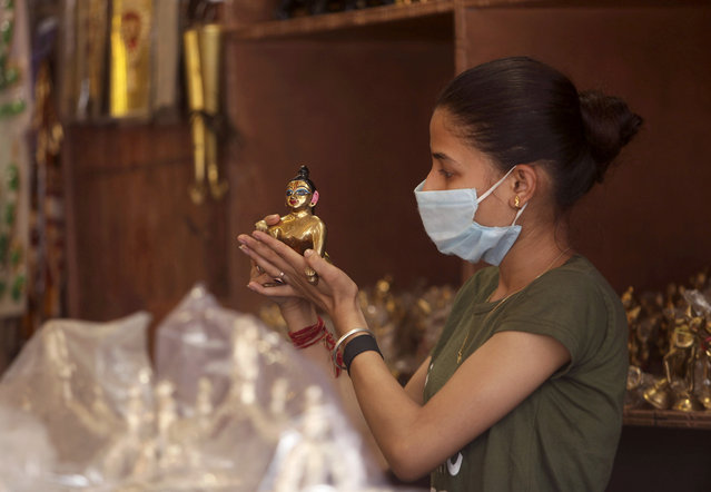 "A girl wearing face mask as a precaution against the coronavirus checks an idol of Hindu god Krishna as she shops ahead of festival ""Janamashtami"" in Jammu, India, Thursday, August 6, 2020. India is the third hardest-hit country by the pandemic in the world after the United States and Brazil. (Photo by Channi Anand/AP Photo)"