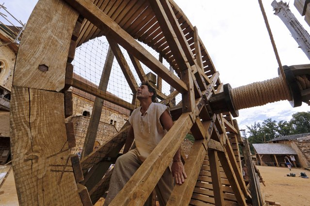 A worker walks in a winch drum at the construction site of the Chateau de Guedelon near Treigny in the Burgundy region of France, September 13, 2016. (Photo by Jacky Naegelen/Reuters)