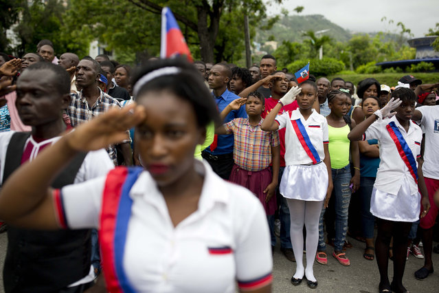 Students salute as the national anthem is played at a ceremony marking Flag Day in Port-au-Prince, Haiti, on May 18, 2017. Haitians celebrated the 214th anniversary of the creation of their national flag Thursday. (Photo by Dieu Nalio Chery/AP Photo)