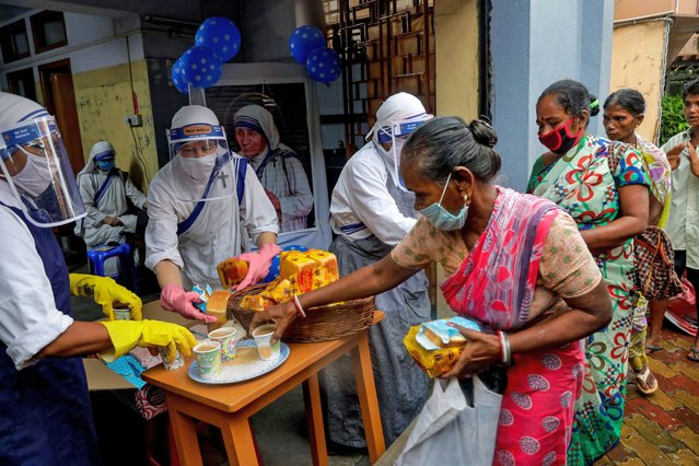 Nuns of the Missionaries of Charity, the order founded by Saint Teresa, wearing masks and face shields as precaution against the coronavirus distribute food to poor and homeless people in Kolkata, India, Wednesday, August 26, 2020. Wednesday marked the birth anniversary of Nobel laureate Mother Teresa, a Catholic nun who spent 45-years serving the poor, the sick, the orphaned, and the dying. (Photo by Bikas Das/AP Photo)