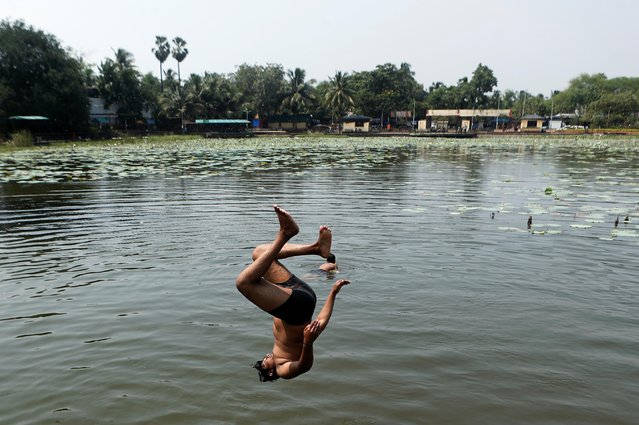 A boy jumps into a pond as the temperature rises in Mumbai, India, September 5, 2020. (Photo by Francis Mascarenhas/Reuters)