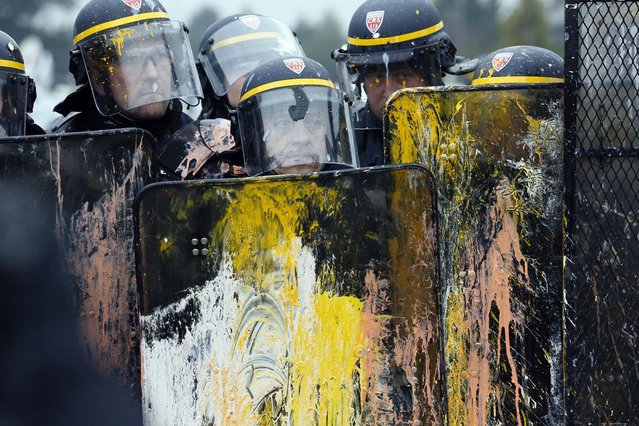 """Anti-riot police hold shields after protestors threw them eggs as US Goodyear Tire & Rubber workers demonstrate in front of the group's headquarters in France, in Rueil-Malmaison, a Paris suburb, on February 12, 2013, at the time of an extraordinary central works council on the plan to shut down Goodyear's plant in Amiens, northern France. """"Closing the factory is the only option after five years of unsuccessful negotiations"""", said a French-language statement issued on January 31, 2013 by Goodyear Dunlop Tires France, which employs about 3,200 people in the country across four sites. (Photo by Patrick Kovarik/AFP Photo)"""