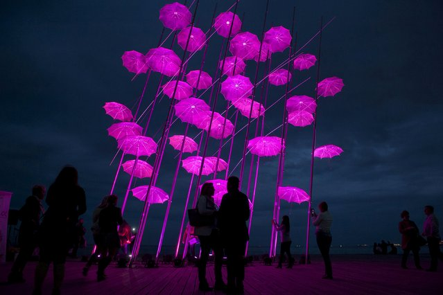 "People stand around ""Umbrellas"", the sculpture by Greek sculptor Giorgos Zogolopoulos, as it is illuminated in pink light to mark Breast Cancer Awareness Month in the northern city of Thessaloniki, Greece, October 21, 2015. (Photo by Alexandros Avramidis/Reuters)"