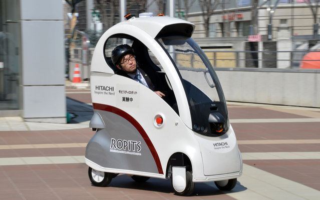 """Japan's high-tech maker Hitachi unveils the new mobility robot """"Ropits"""" (Robot for Personal Intelligent Transport System) in Tsukuba in Ibaraki prefecture on March 12, 2013. The one man mobility robot can pick-up and drop off a passenger autonomously, while the vehicle can be controled by a joystick controler in the cockpit. (Photo by Yoshikazu Tsuno/AFP Photo)"""