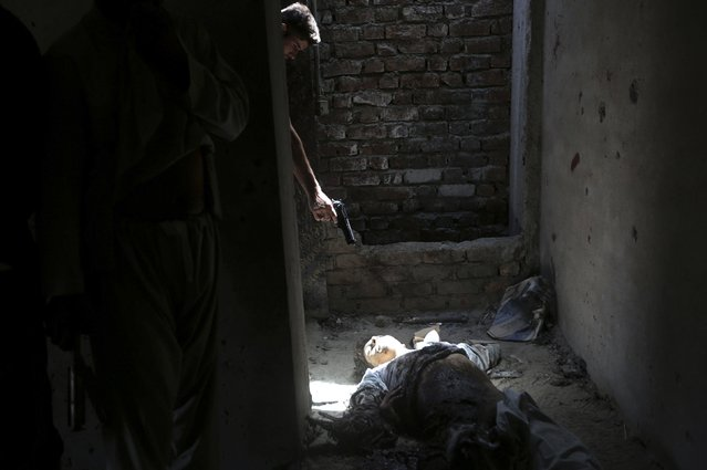 An Afghan resident points his weapon at the dead body of an unidentified militant, as a way of showing his hatred for insurgents, at a building where three other militants were located, after an attack in Kabul, in this July 17, 2014 file photo. (Photo by Omar Sobhani/Reuters)