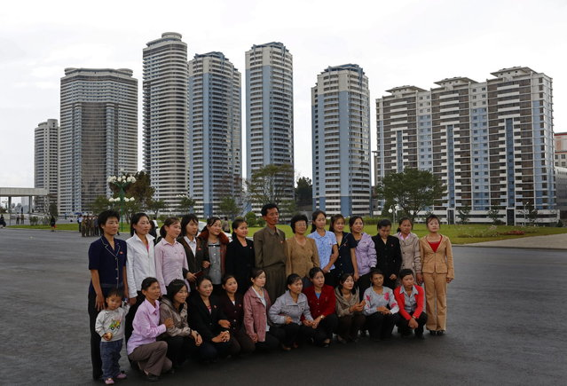 A group of North Koreans pose for a picture near the newly constructed development project area on Mansu Hill in Pyongyang, North Korea Wednesday, September 19, 2012. (Photo by Vincent Yu/AP Photo)