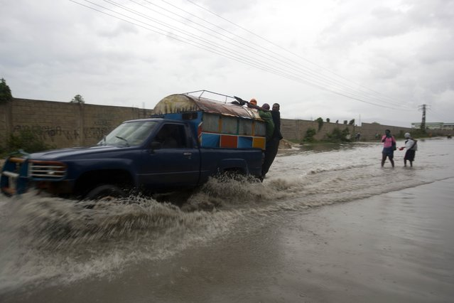 "A ""tap-tap"" truck carrying commuters drives through a street flooded by rain brought by Hurricane Matthew in Port-au-Prince, Haiti, Tuesday October 4, 2016. Hurricane Matthew roared into the southwestern coast of Haiti on Tuesday, threatening a largely rural corner of the impoverished country with devastating storm conditions as it headed north toward Cuba and the eastern coast of Florida. (Photo by Dieu Nalio Chery/AP Photo)"