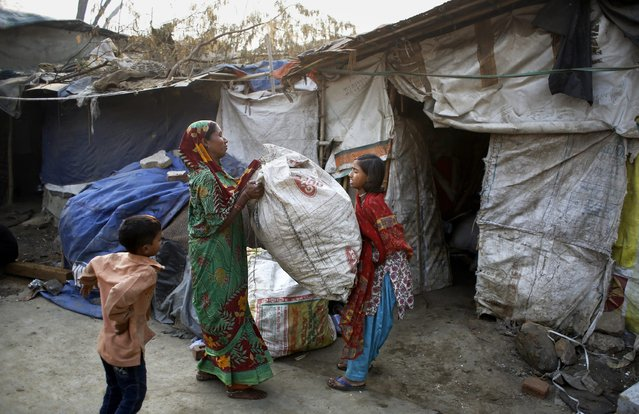 In this November 11, 2014 photo, Murshida, 12, helps her mother Marjina lift a sackful of trash for segregation outside their rented shanty on the outskirts of New Delhi, India. (Photo by Altaf Qadri/AP Photo)